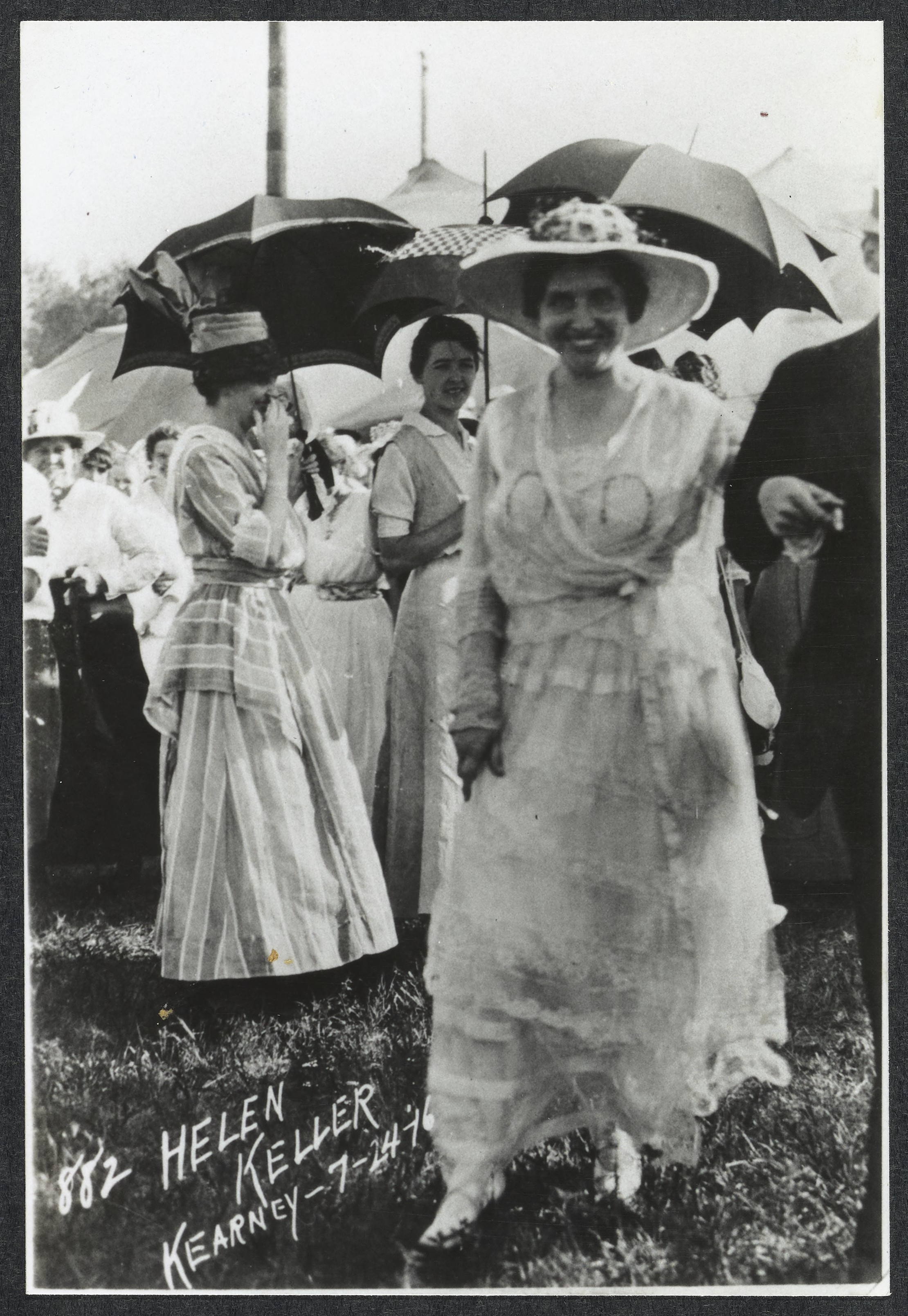 Helen Keller circa 1916. Helen Keller outdoors, wearing a white dress and a broad hat, striding towards the camera. Behind her, women with parasols gather and mingle.